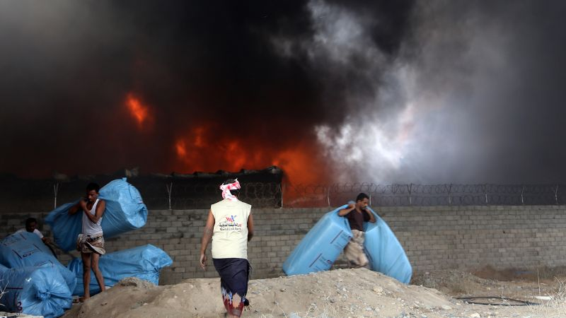 Yemeni workers evacuate food bags as fire engulfs a rebel-held United Nations' World Food Program warehouse in 2018 | ABDO HYDER/AFP/Getty Images