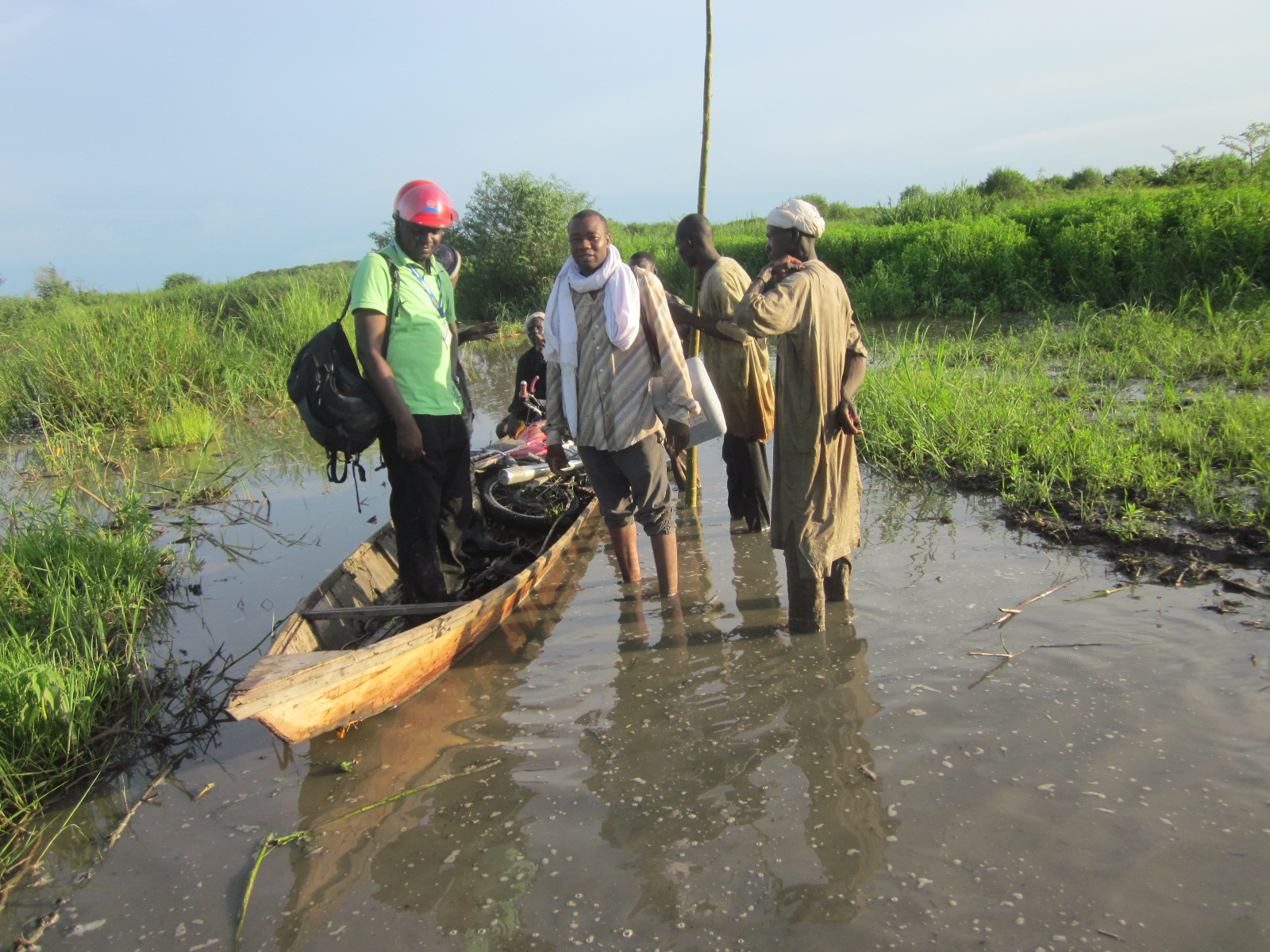STOP team members boards a canoe to travel through the flooded areas of Chad to vaccinate children