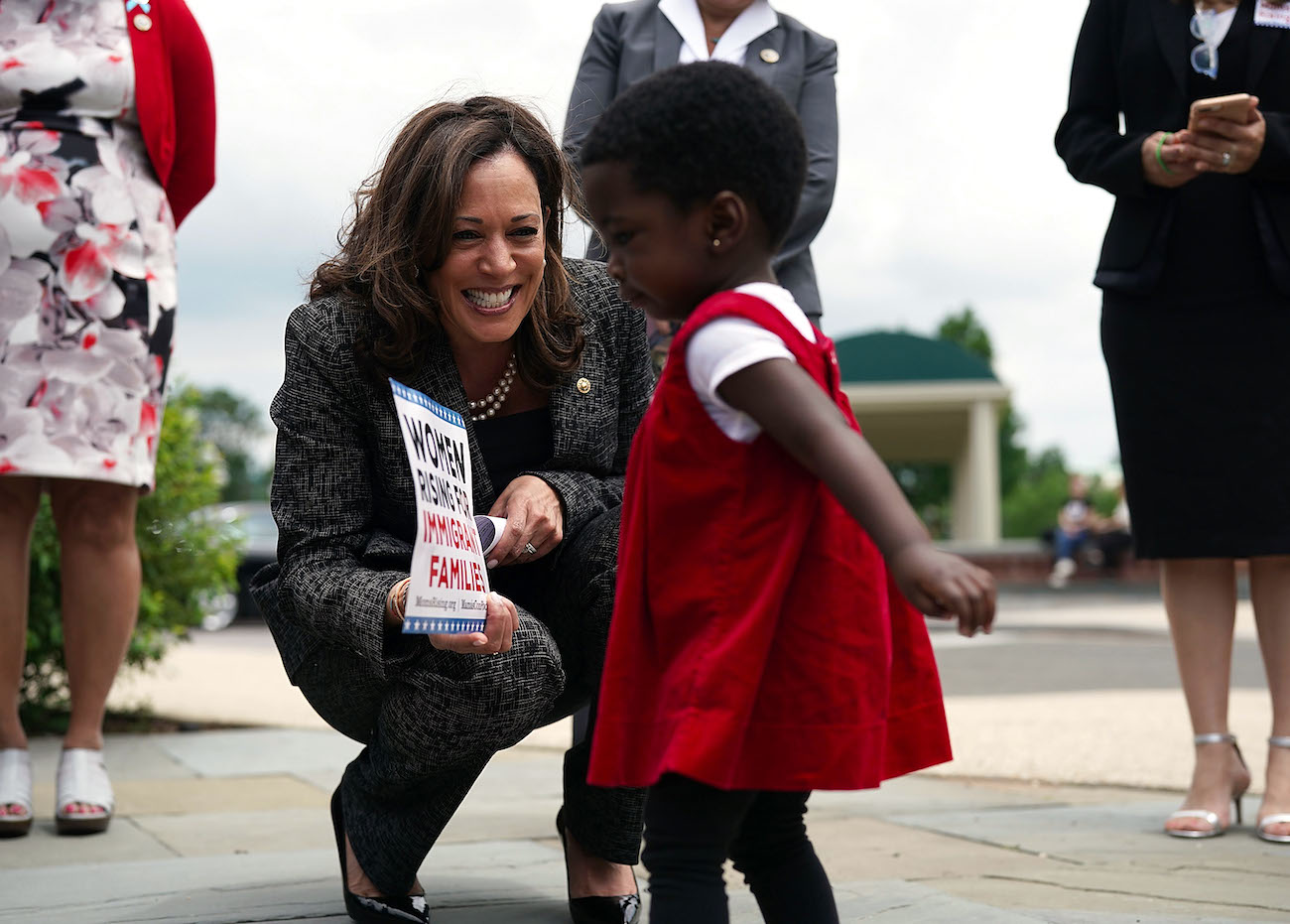 "Vice President Elect Kamala Harris plays with 18-month-old Hawa Tembe (R), whose mother is an immigrant from Mozambique, during a 2018 news conference to ""to show support for immigration and refugee policies that protect the rights and safety of women and children."" 