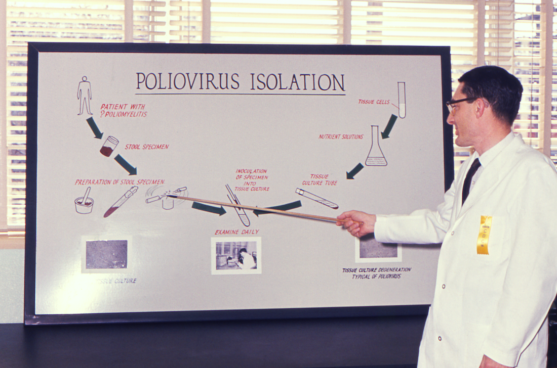 A public health scientist in 1961 explaining the laboratory techniques involved in the isolation of the poliovirus.
