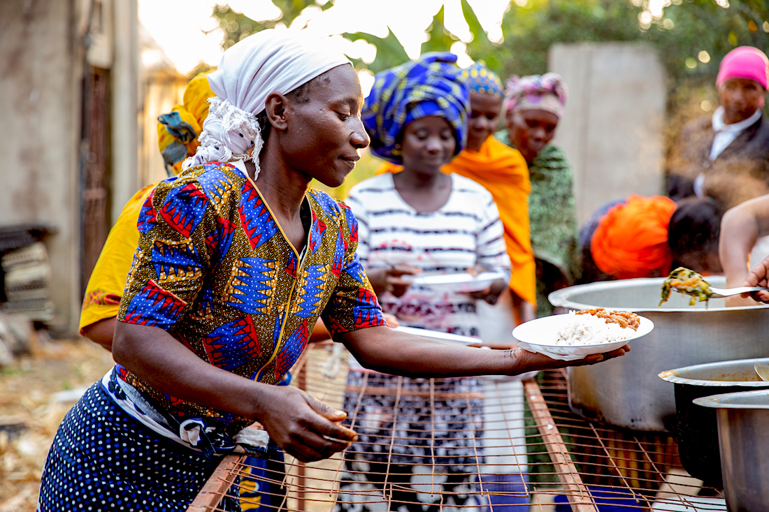 A woman hand out food at a cooking demonstration