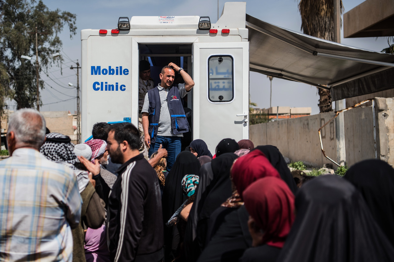 A solitary aid worker looks on as people queue for treatment from his mobile clinic during fighting in Iraq in 2017