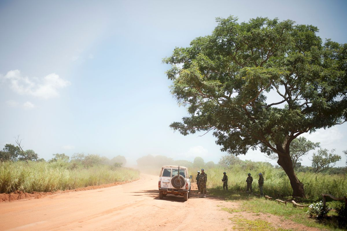 A UN patrol of the Multidimensional Integrated Stabilisation Mission in the Central African Republic wait under a tree for the arrival of the convoy they will escort along the only supply road to the capital in 2017 | FLORENT VERGNES/AFP/Getty Images