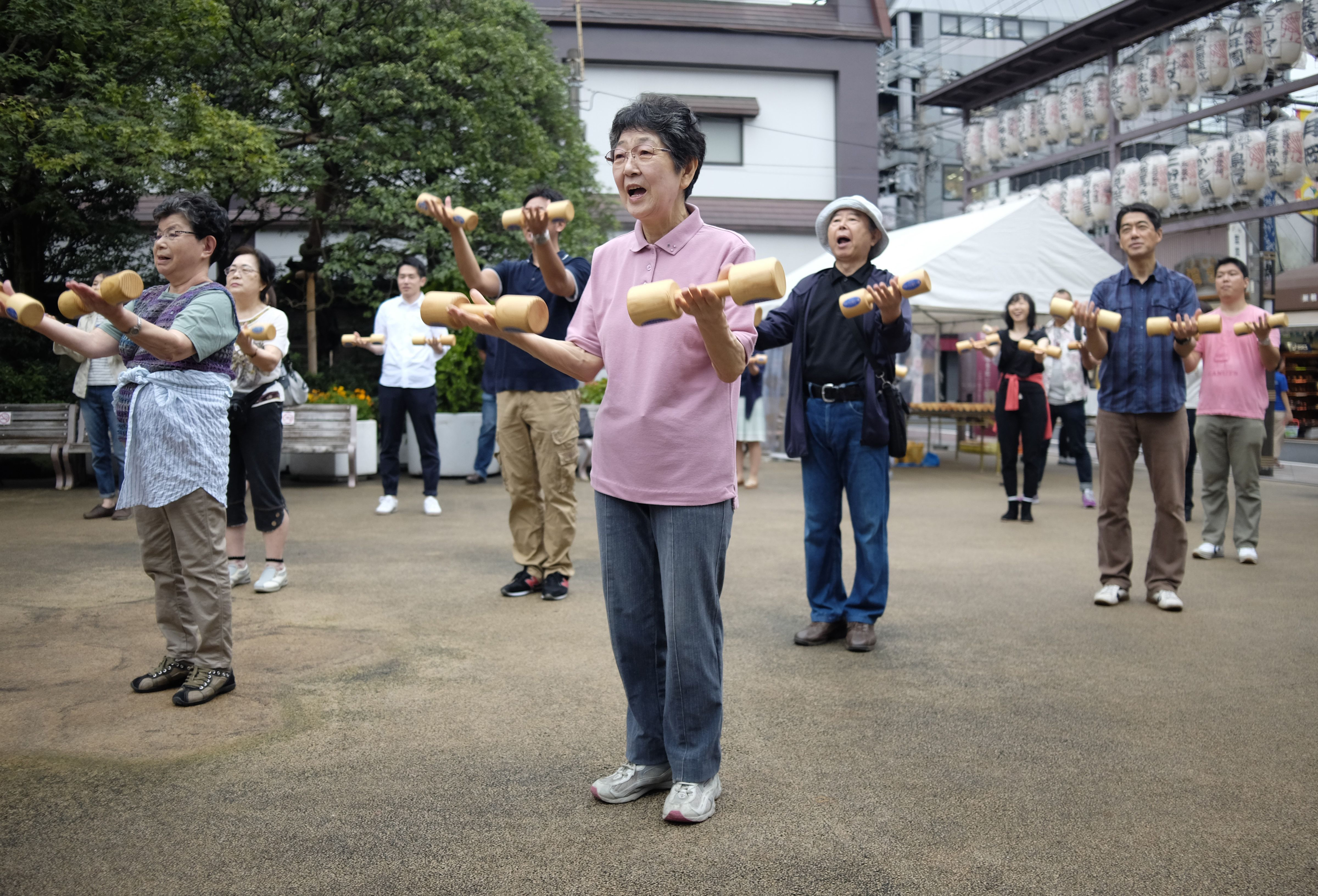 Elderly people work out with wooden dumb-bells in the grounds of a temple in Tokyo.