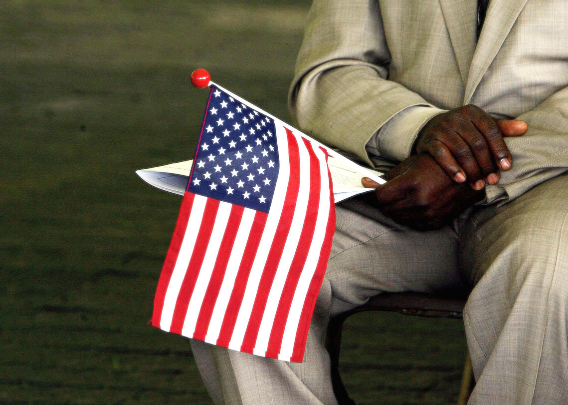 A man originally from Sierra Leone holds a US flag while waiting to become a US citizen during a naturalization ceremony in 2006. | JIM WATSON/AFP via Getty Images