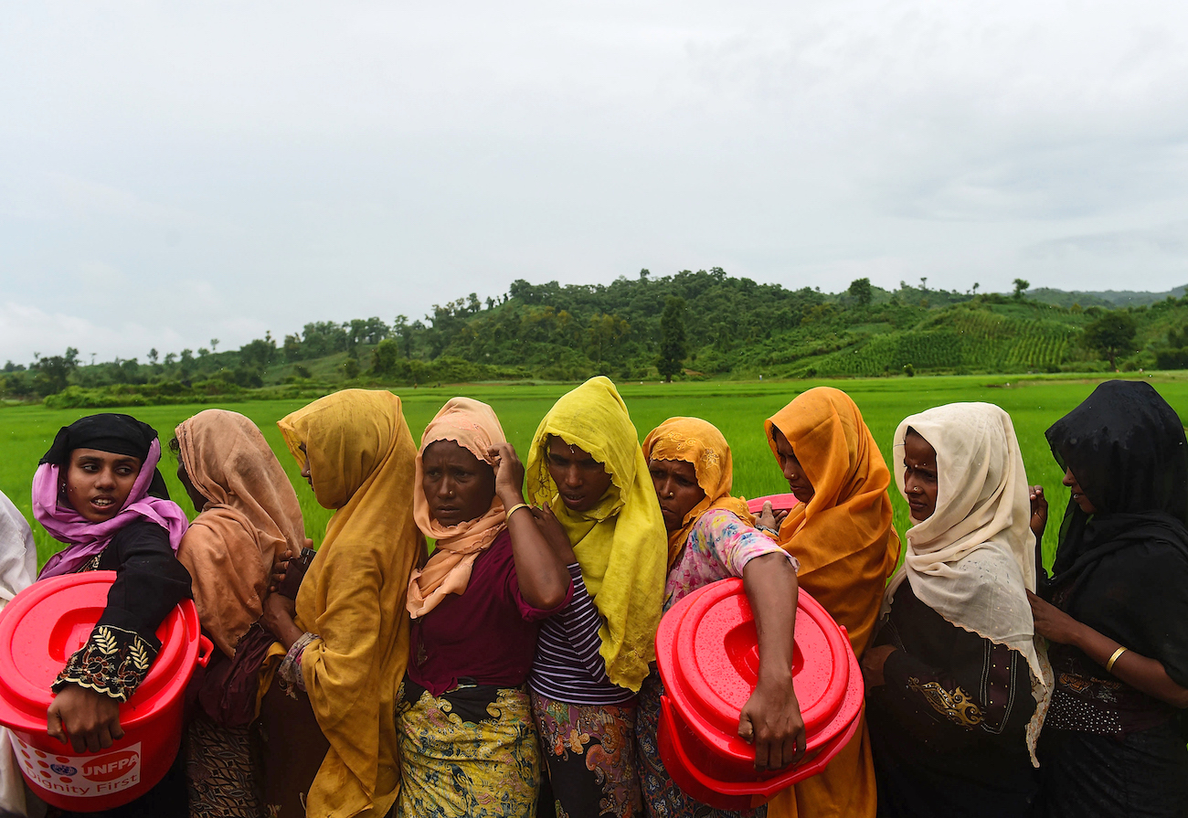 Rohingya Muslim refugees wait in line for relief supplies after fleeing burning villages, the army and ethnic Rakhine mobs