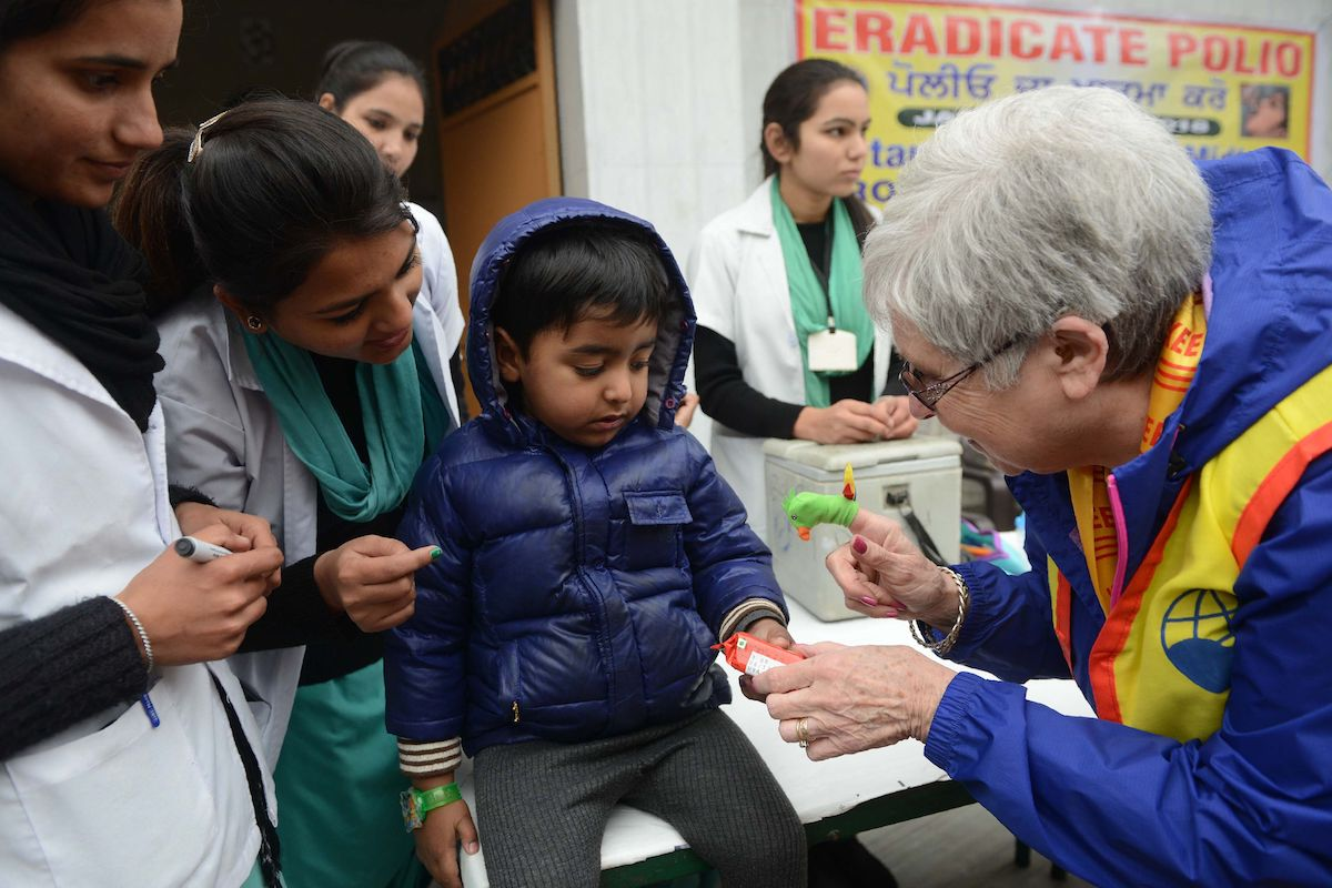 A member of Rotary Club give biscuits to a child after he receives polio vaccine drops | NARINDER NANU/AFP/Getty Images