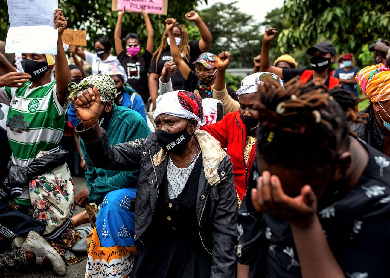 Kevin Gitau's mother (C) wears a mask with her son's name, who was killed by Kenyan Police during a nigh curfew, as she raises her fist in front of the Kenyan Parliament during their protest against police brutality in Nairobi on June 9, 2020.