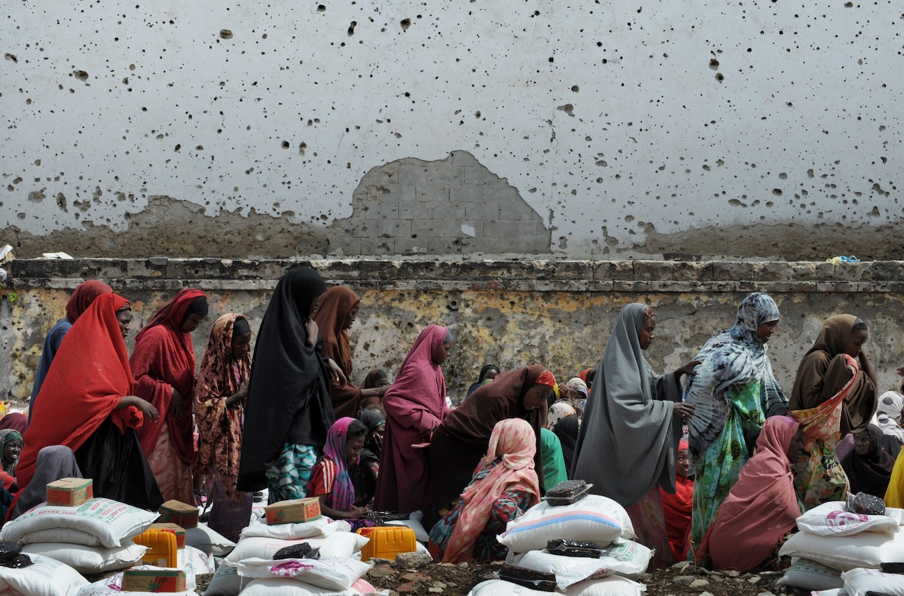 Somali women who fled drought and violence wait beneath a bullet scarred wall to collect aid