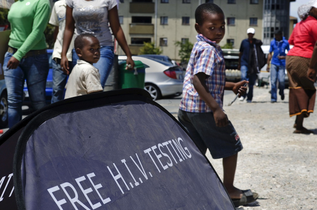Children walk past a US funded mobile AIDS testing unit in Cape Town