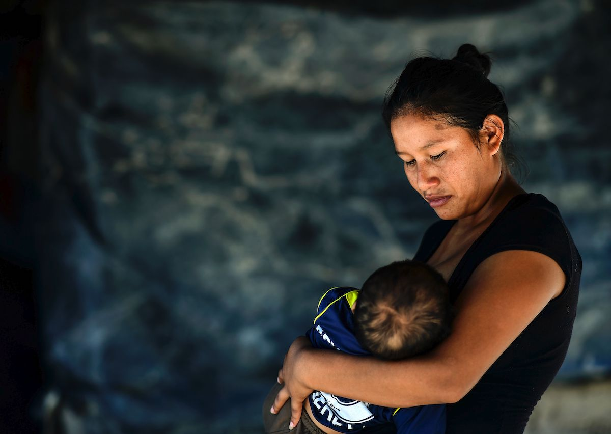 An indigenous Wichi woman breastfeeds her son in northern Argentina where inadequate access to safe drinking water and nutritious food has contributed to child mortality.   RONALDO SCHEMIDT/AFP via Getty Images