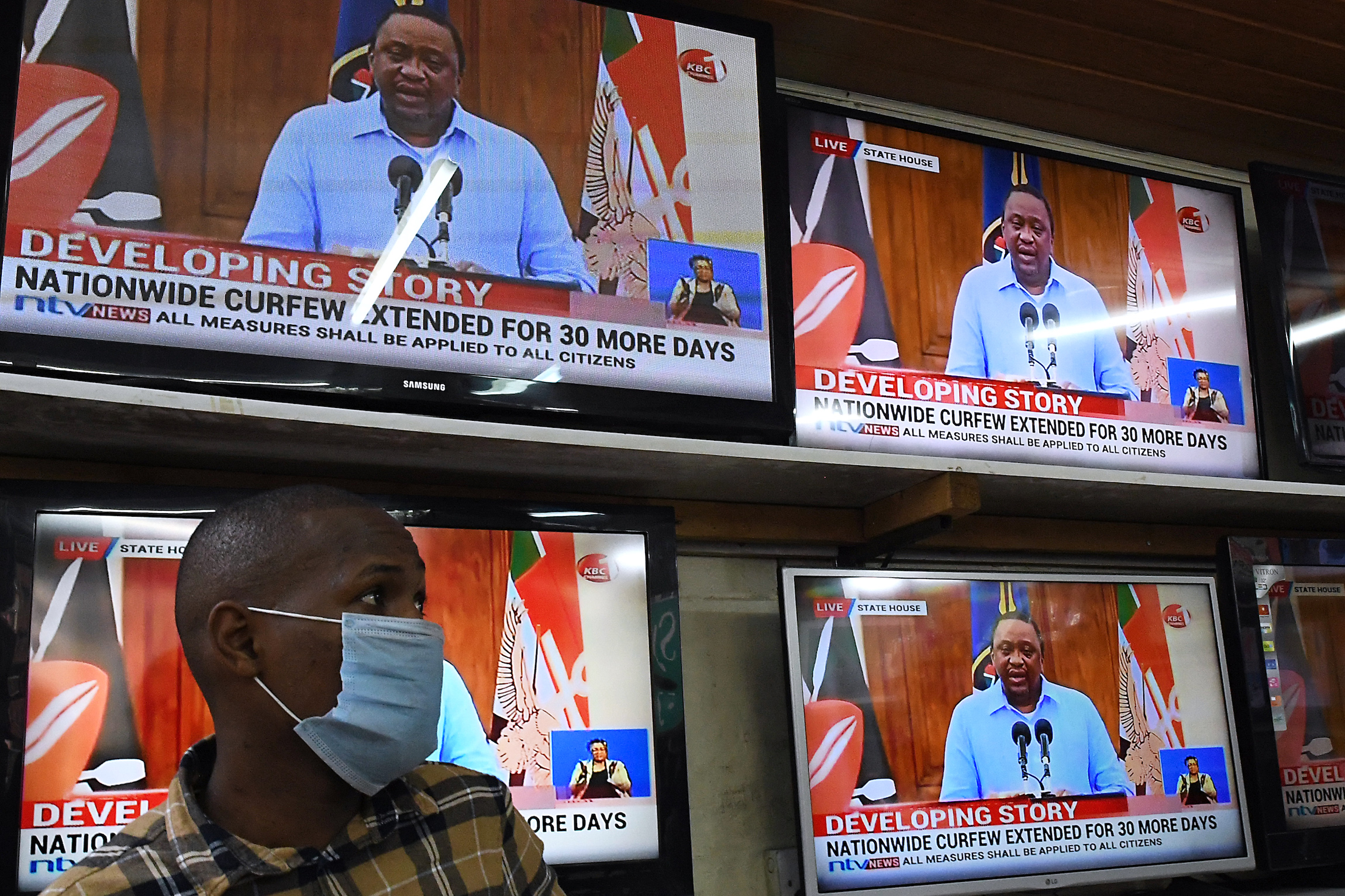 An electronics shop assistant watches on television Kenya's President Uhuru Kenyatta giving a state of the nation address on the coronavirus (COVID-19) pandemic.