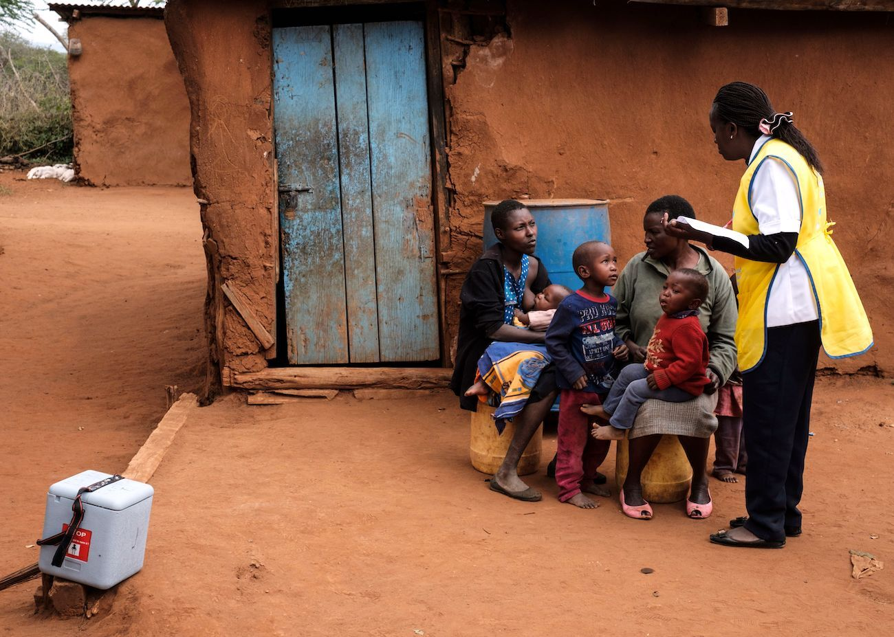 A nurse (R) talks with mothers at their home about polio vaccines.