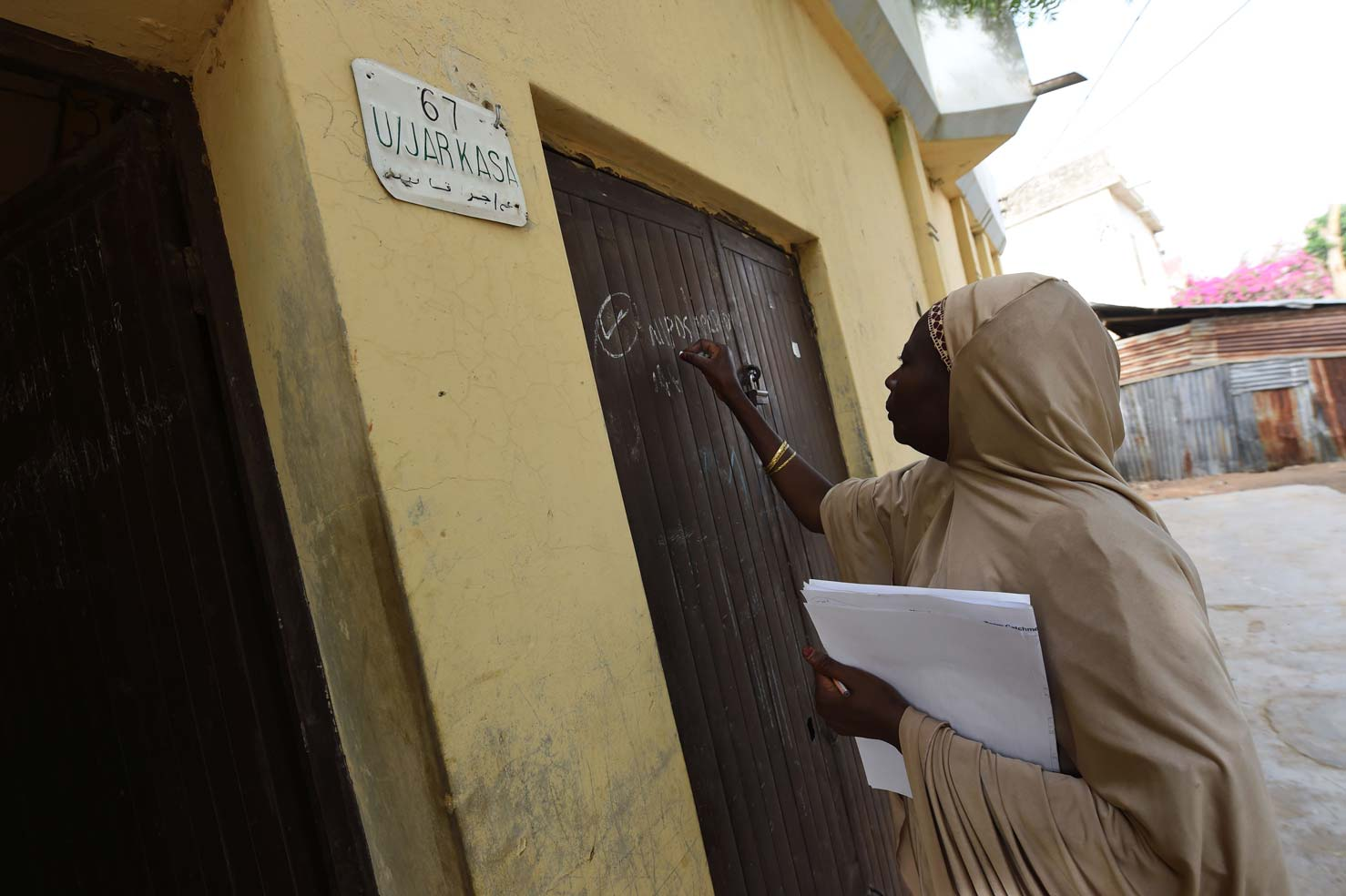 A health worker marks the gate of a house which was visited during a vaccination campaign against polio at Hotoro-Kudu