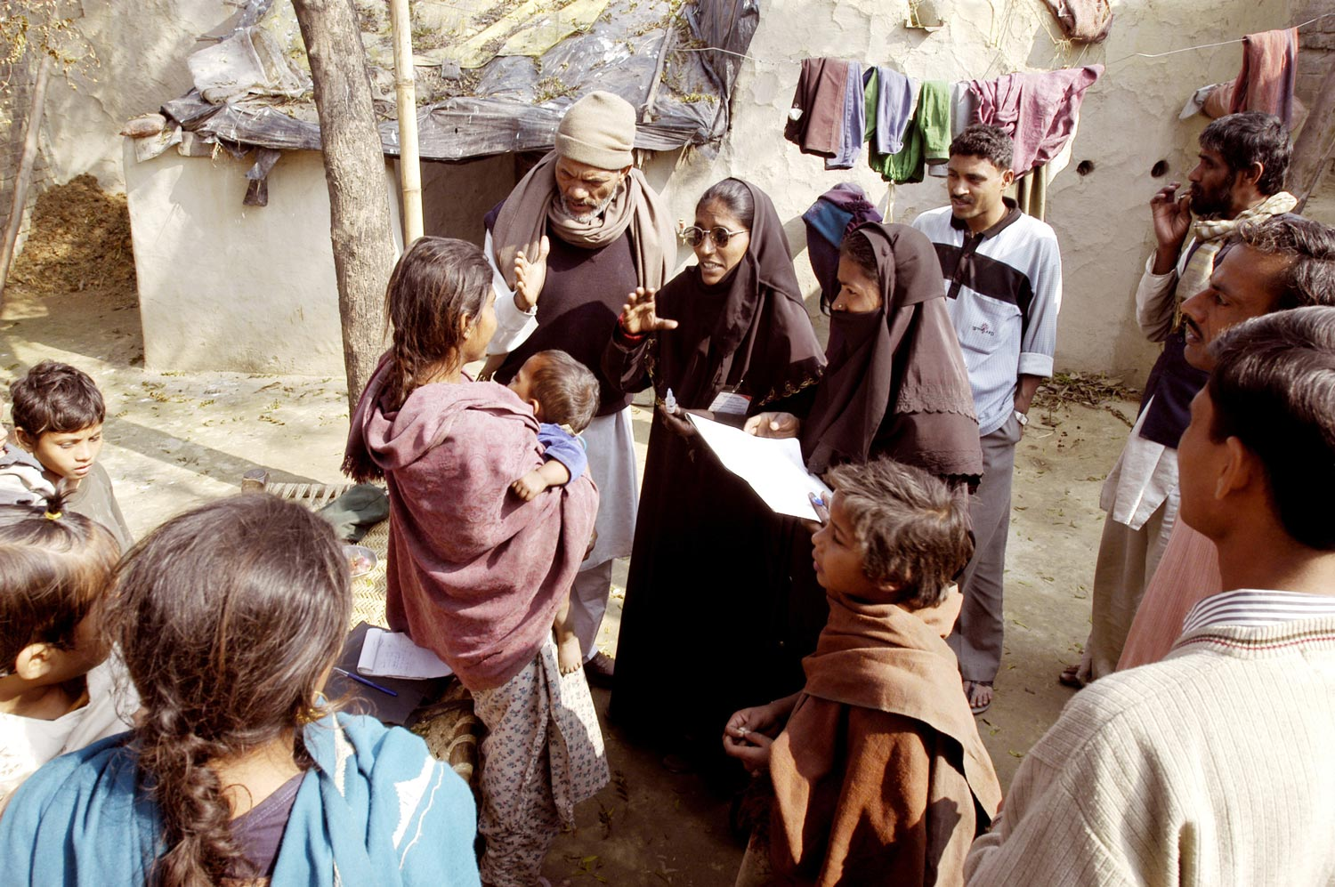 Health workers and villagers try to convince a woman to let her children be vaccinated against polio in Moradabad