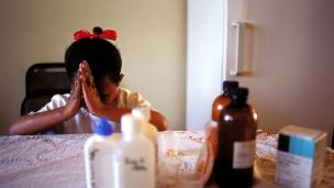 A nine-year-old girl in Johannesburg prays before taking her antiretroviral HIV-AIDS drugs.