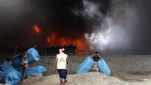 Yemeni workers evacuate food bags as fire engulfs a rebel-held United Nations' World Food Program warehouse in 2018   ABDO HYDER/AFP/Getty Images