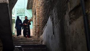 Two Pakistani health workers arrive at a house to vaccinate children