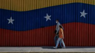 A couple wearing face masks walks past a wall painted as the Venezuelan national flag in Caracas on April 17, 2020, amid the novel coronavirus (COVID-19) outbreak. | FEDERICO PARRA/AFP via Getty Images