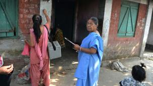 Indian health workers mark the wall of a house to show children there have received the polio vaccine